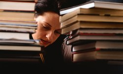 A WOMAN, A STUDENT, STUDYING, SURROUNDED BY BOOKS